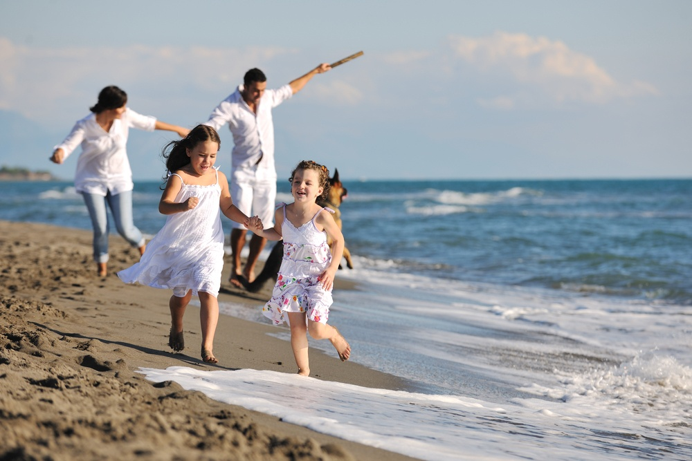 happy young family in white clothing have fun and play with beautiful dog at vacations on beautiful beach.jpeg